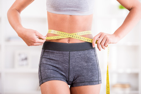 weight: Sporty woman and measure around her body at home.