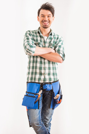 home repair: Portrait of young, smiling man with tools for home repair.