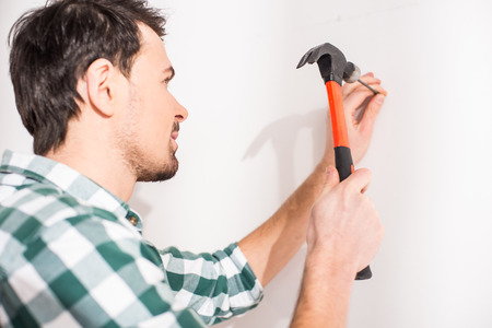 Repair home concept. Young man hammer a nail. Stock Photo