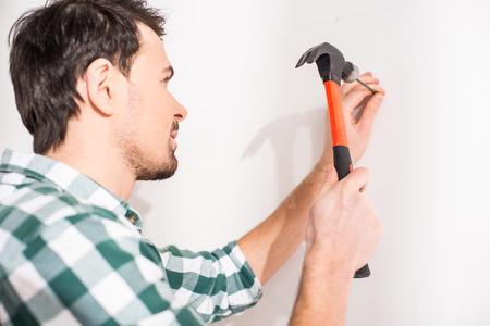 Repair home concept. Young man hammer a nail. Foto de archivo