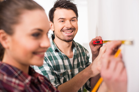 Repair home concept. Young couple are measuring a wall with measuring tape.