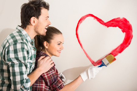 Young happy couple are painting a heart on the wall while doing repair at home. photo