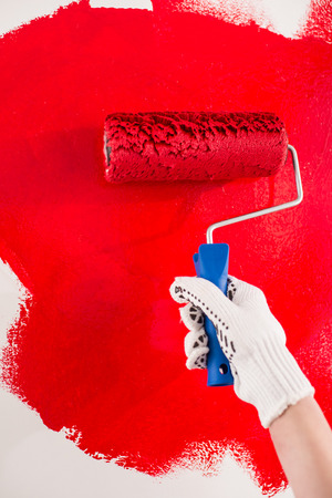 Close-up of hand with roller is painting a wall  in red. photo