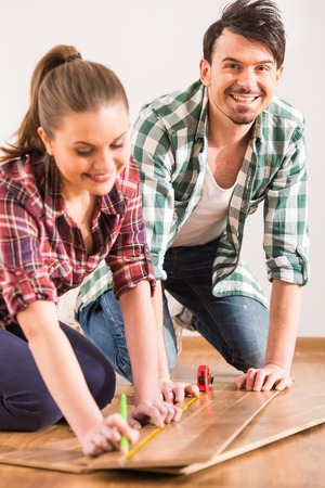laminate flooring: Young couple are installing laminate flooring in the room.