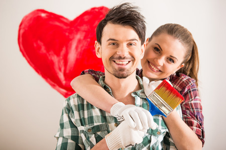 Portrait of young happy couple painted a heart on the wall while doing repair at home and looking at the camera.