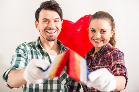 Portrait of young happy couple painted a heart on the wall while doing repair at home and looking at the camera. photo