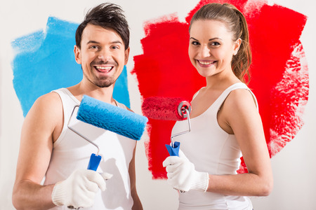 Young couple are doing repair at home and painting a wall with roller. photo