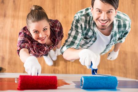 Bovenaanzicht van jong koppel doen reparatie thuis en schilderen een muur met roller.