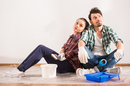 Tired young couple are sitting on the floor with paint brush and bucket  while doing repair at home. photo