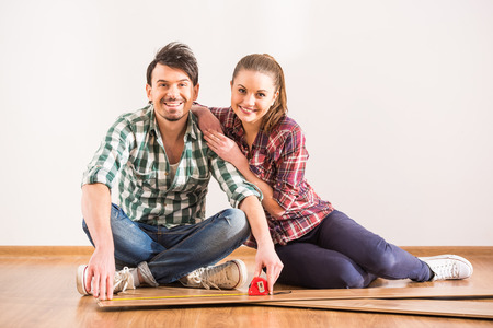 redesign: Young couple are installing laminate flooring in the room.
