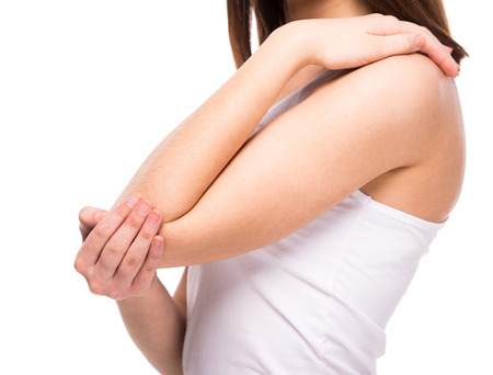 Acute pain in a woman elbow. Female is holding hand to spot of elbow pain indicating location of the pain. Isolation on a white background.