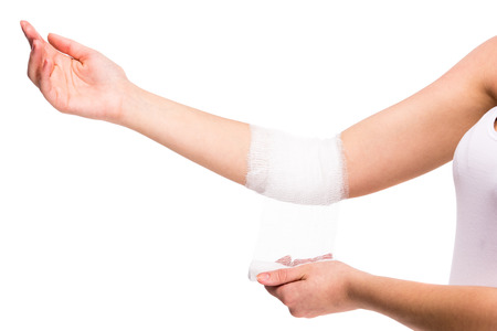 Close-up hand of woman, injured painful elbow with white bandage.
