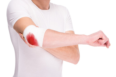 Close-up hand of man, injured painful elbow with white bloody bandage.