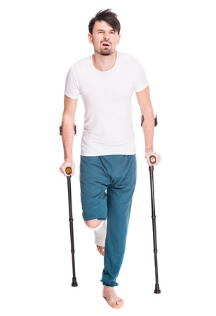 Full length portrait of a young man with broken leg is using crutch isolated on white background.