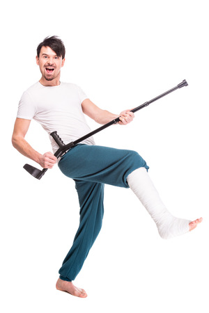Full length view of a smiling man with broken leg is using crutch and dancing isolated on white background.
