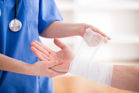 Close-up female doctor is bandaging upper limb of patient.