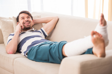 Young man is lying on sofa with broken leg and talking by phone. Stock Photo