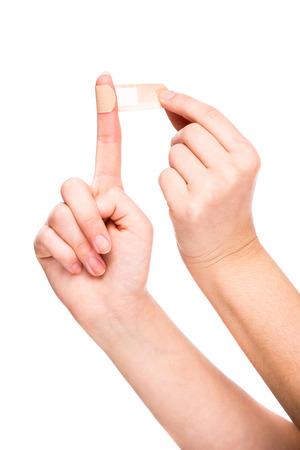 Close-up van vrouw met hechtpleister op vinger. Geïsoleerd op wit.