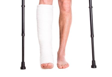 crutches: Close-up patient with broken leg in cast and bandage.