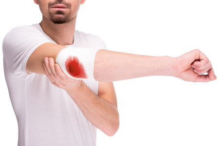 elbow bandage support: Close-up hand of man, injured painful elbow with white bloody bandage.