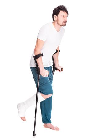 pierna rota: Vista de la longitud completa de un hombre joven con la pierna rota es usando muleta aislado sobre fondo blanco. Foto de archivo