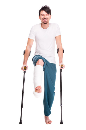 Full length portrait of a smiling man with broken leg is using crutch isolated on white background.