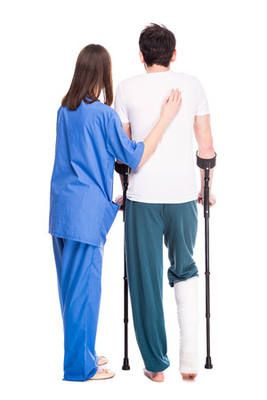 plaster leg cast: Back view of experienced physician assistant her patient in recovery process. Isolated on white. Stock Photo