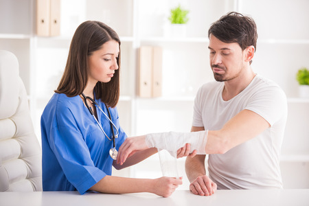 Pretty female doctor is bandaging upper limb of young man.