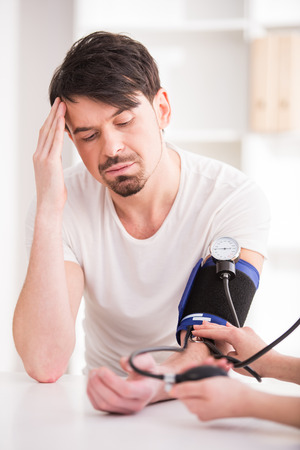 hypertension: The doctor measures the pressure to young man with headache.