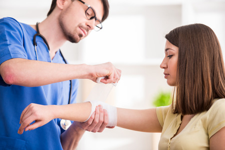 upper limb: Confident male doctor is bandaging upper limb of young woman.