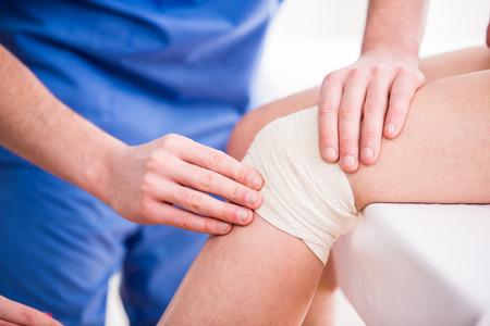 fractura: El doctor est� rebobinando vendaje de la rodilla a la mujer joven.