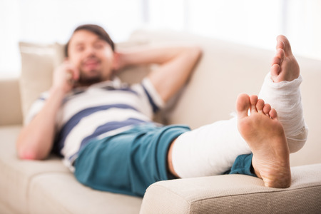 cast: Young man is lying on sofa with broken leg and talking by phone. Stock Photo