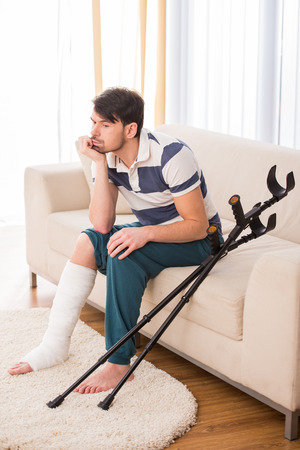 Young sad man is sitting on sofa with broken leg.