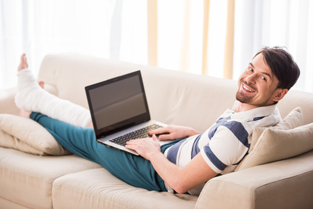 Young smiling man is sitting on sofa with broken leg and using laptop.