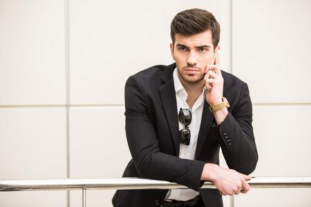 Ritratto di giovane uomo alla moda sta parlando per telefono.