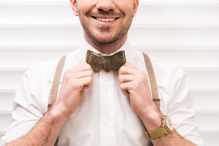 Smiling, young man with suspenders and bow-tie.