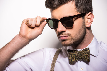 Portrait of young trendy man with black glasses and bow-tie on gray background. Stock Photo