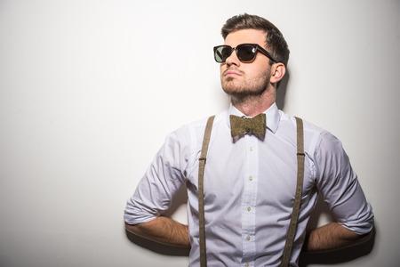 Portret van jonge trendy man met zwarte bril, jarretels en bow-tie op grijze achtergrond.