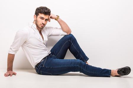 Schöne, junge, trendige Mann sitzen auf dem Boden im Studio auf grauem Hintergrund.
