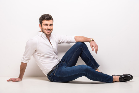 white shirt: Handsome, young, trendy man is sitting on the floor in studio on gray background.