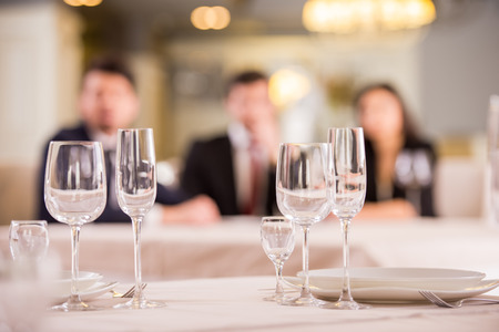 business lifestyle: Focus on empty glasses. Three business partners are meeting in restaurant on background.