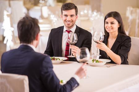 comiendo: Almuerzo de trabajo. Reuni�n del equipo en restaurante, comer y beber en la celebraci�n de un buen trabajo juntos. Foto de archivo