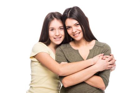 madre e hija adolescente: Hermosa madre y su hija linda sonriendo y posando en el fondo blanco. Foto de archivo