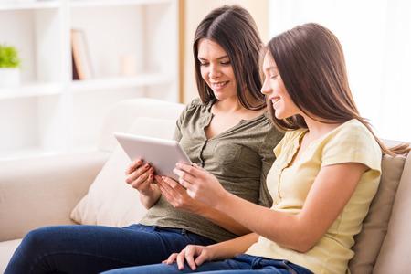 jeune fille adolescente: Belle mère et sa fille adolescente mignonne utilisent tablette numérique alors qu'il était assis sur le canapé à la maison.