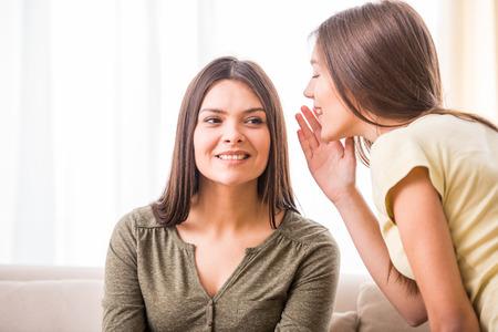 madre e hija adolescente: Hija adolescente está susurrando algo a su madre.