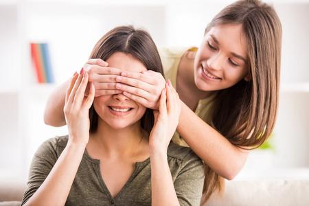 madre e hija adolescente: Sonriendo hija adolescente cierra los ojos a su mamá.