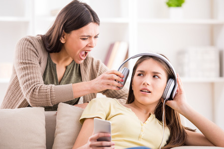 adolescencia: Los problemas entre generaciones concepto. Adolescente cerró los oídos con el auricular mientras que su mamá le grita. Foto de archivo
