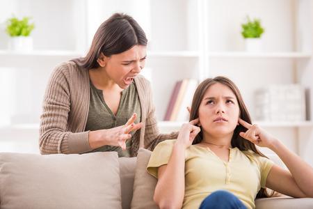 madre e hija adolescente: Los problemas entre generaciones concepto. Adolescente cerr� los o�dos con las manos, mientras que su madre le grita.