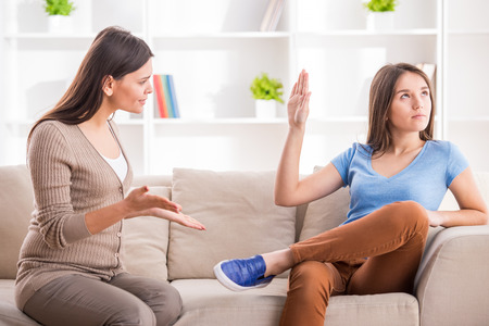 people arguing: Teen girl is showing stop gesture to angry mother while sitting on sofa at home.