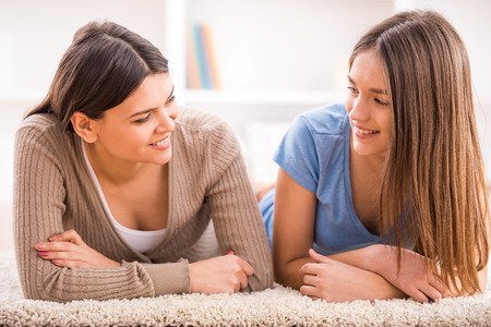 parenthood: Smiling mother and her teen daughter are lying on the floor and looking at each others.